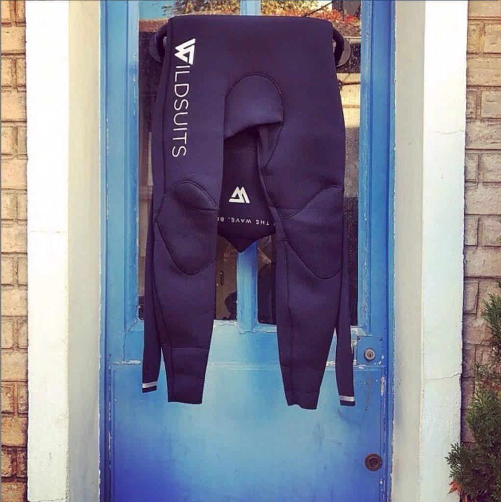 Combinaisons Wildsuits qui sèche sur un support Godry Hanger  sur une porte bleue.
